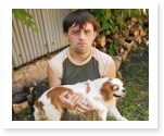 Man with down syndrome holding dog.